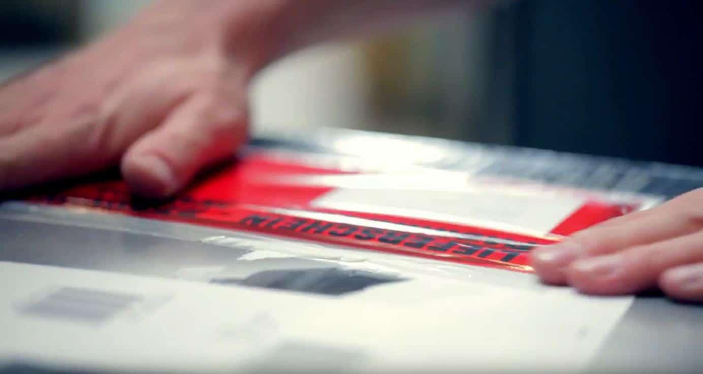 Ein Paket wird mit einem Aufkleber versehen - Direktvertrieb eCommerce Produktion