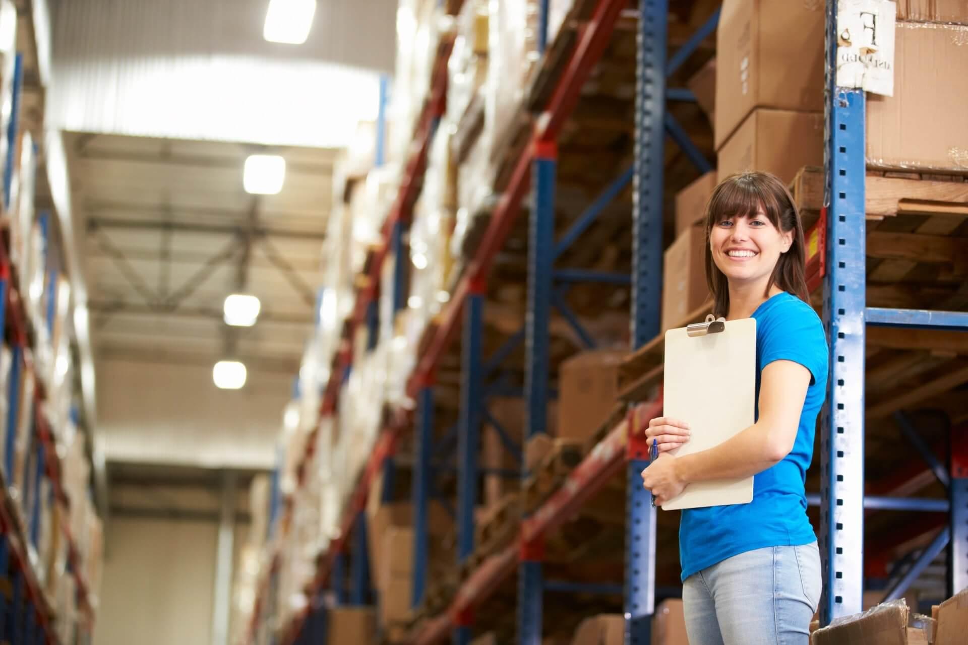 Eine lächelnde Frau im blauen T-Shirt steht mit Klemmbrett im Lager und führt Buch für das ERP System