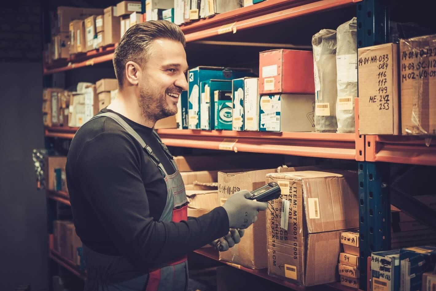 Ein Mitarbeiter eines Onlinehandels steht im Lager und scannt Produkte mit dem MDE Gerät - Handscanner