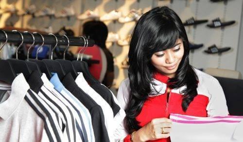 Artikelchecklisten - eine Frau mit dunklen Haaren begutachtet ein Shirt in einem Modegeschäft
