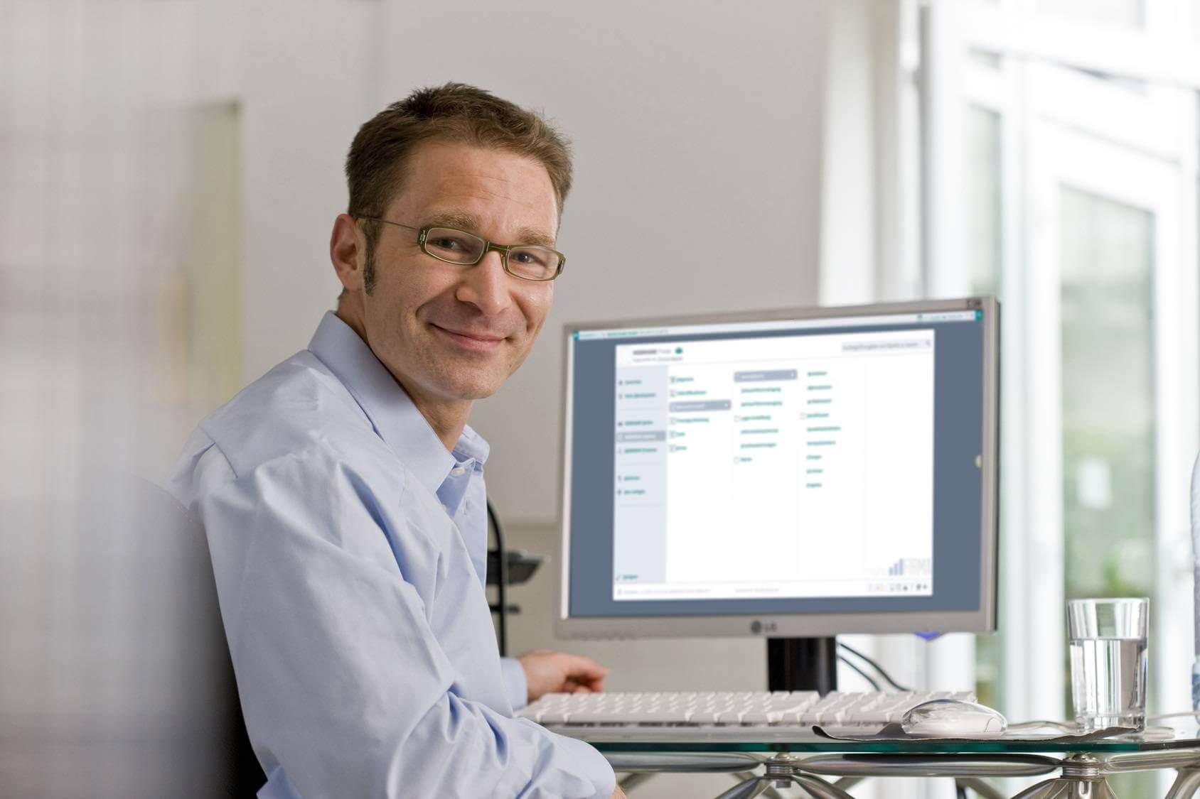 Ein Mann mit WEBWARE Bildschirm im Hintergrund - Softwarebetreuung Festpreis Kunde