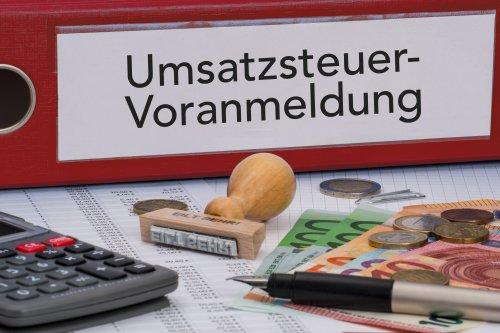 Aktenordner (rot) mit Beschriftung Umsatzsteuer-Voranmeldung und Geld daneben