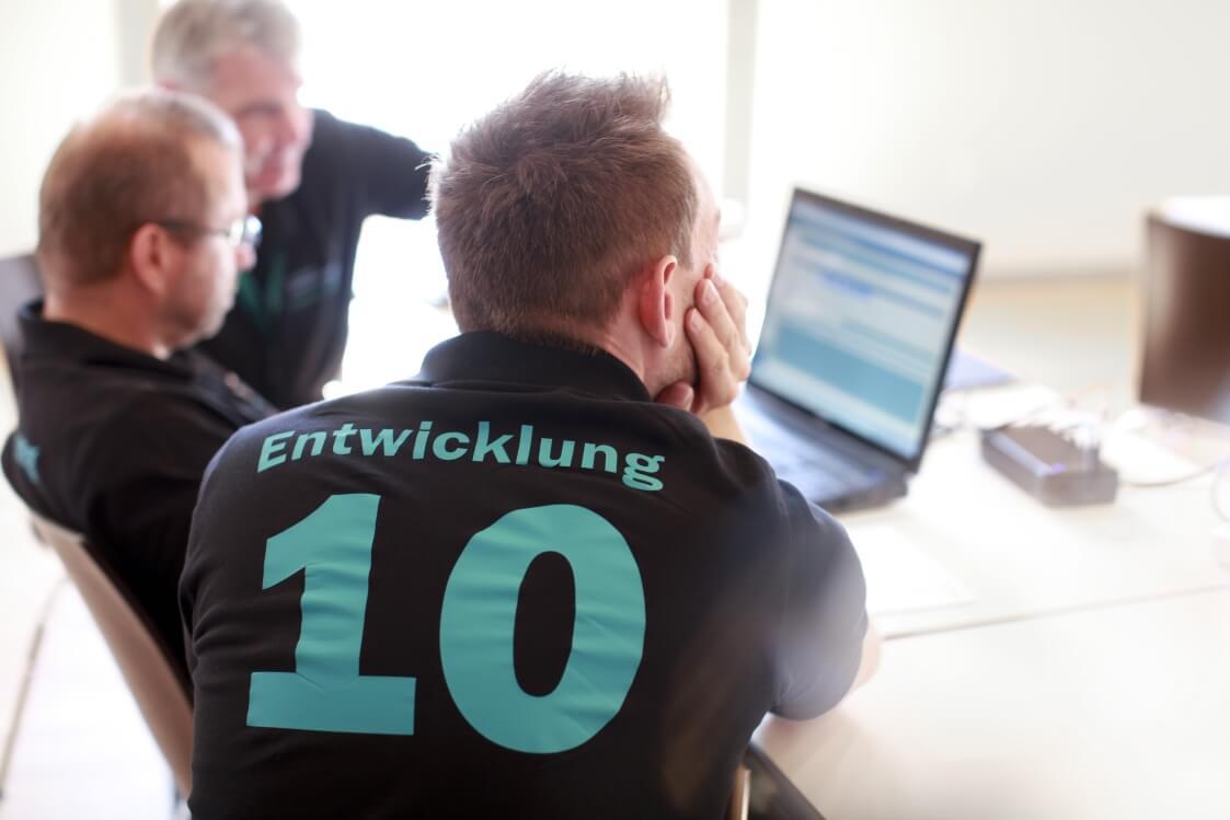 Entwicklerteam sitzt vor einem Laptop und berät sich - ERP Lösung