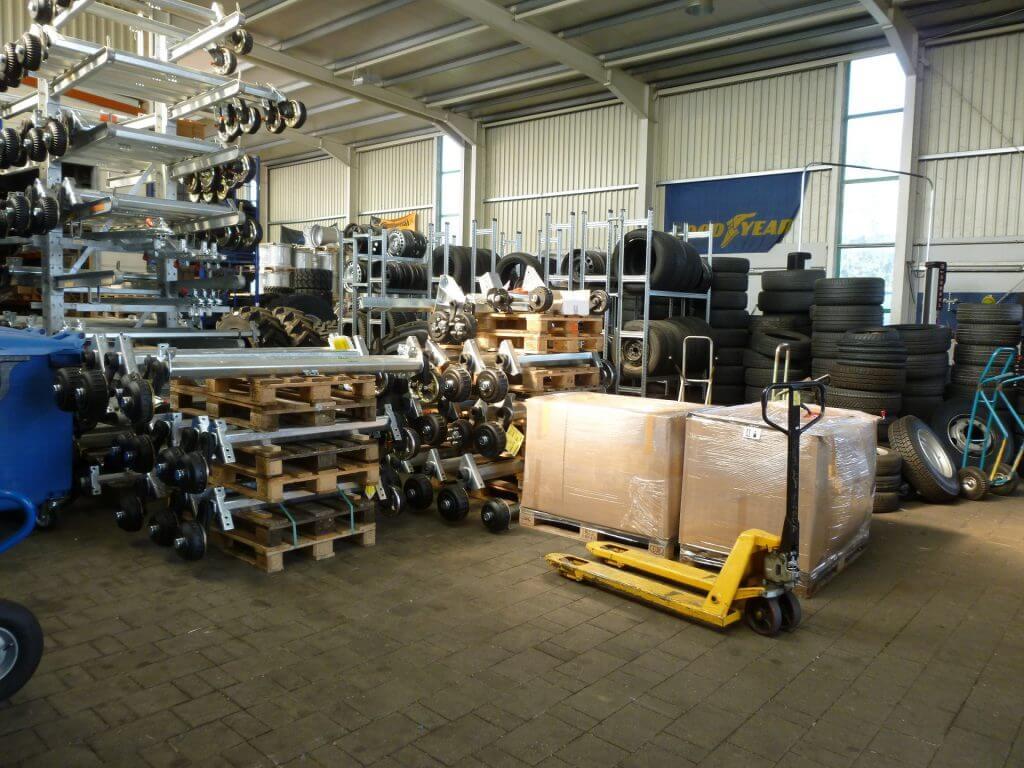Lager der Firma Irmi Fischbacher mit gestapelten Reifen, Paketen und diversen Rollen