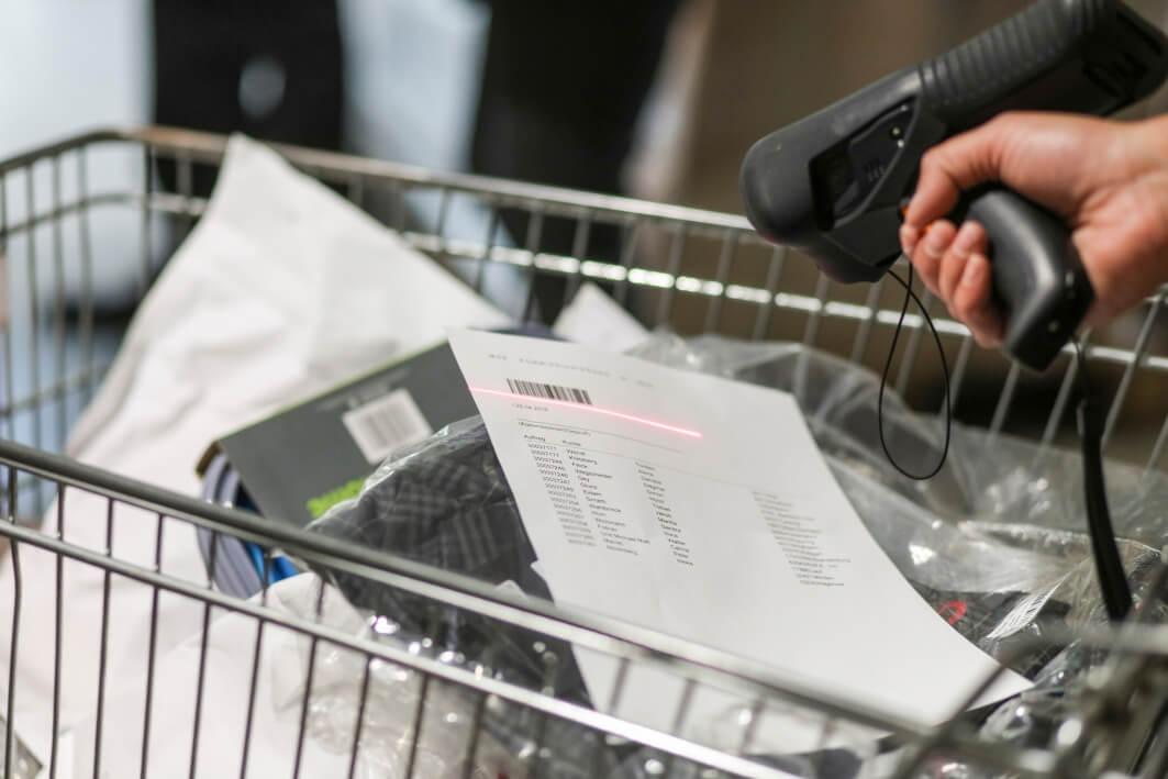 MDE-Gerät wird benutzt um den Barcode einer Liste, die in einem vollen Einkaufswagen liegt, verwendet