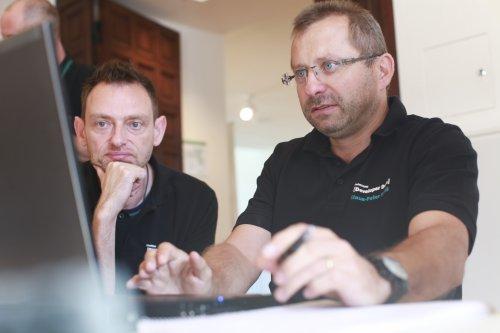 Präsentationsphase des ERP-Systems - drei Menschen beobachten eine Bildschirmpräsentation