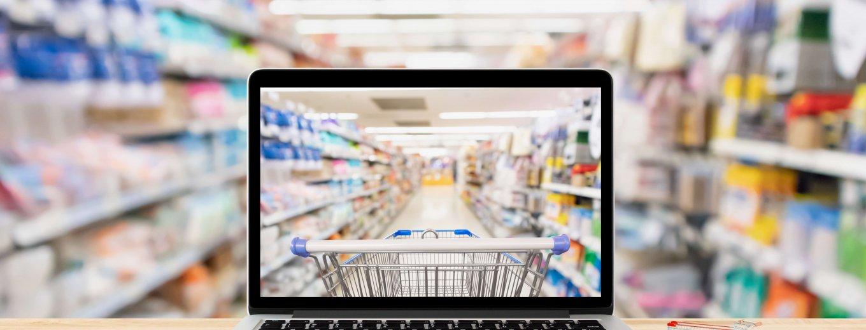 Laptop auf einem Tisch der vor Warenregalen steht und durch das Display vor einem Einkaufwagen steht
