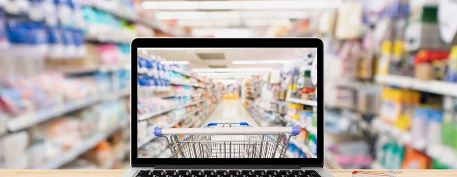 Laptop auf einem Tisch der vor Warenregalen steht und durch das Display vor einem Einkaufwagen steht - E-Commerce