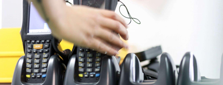 zwei MDE-Geräte stehen nebeneinander in der Aufladestation - eine Hand greift nach dem rechten Gerät - für die Inventur