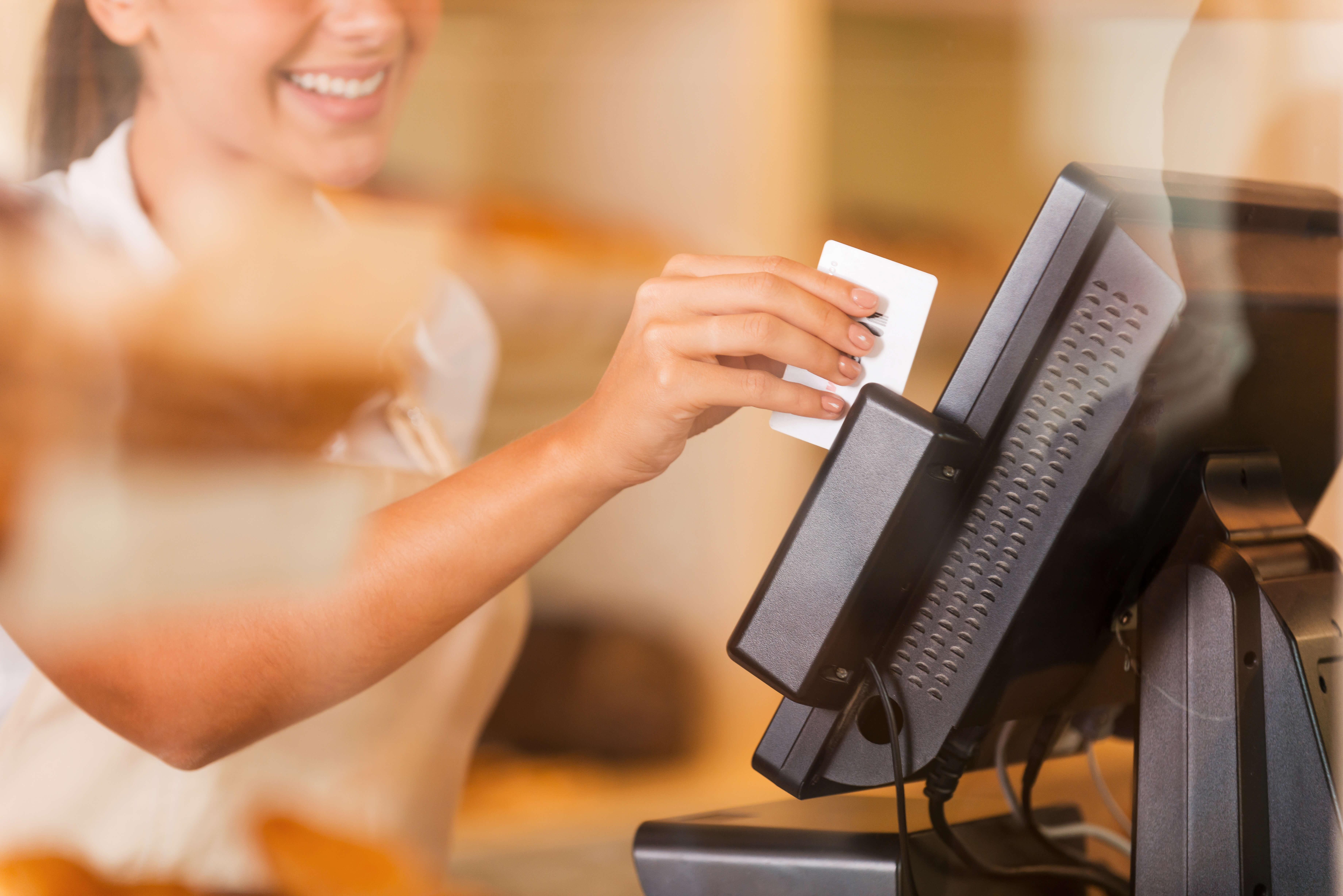 Kassiererin zieht eine Karte durch ein Kassensystem - Nutzung Fördermittel
