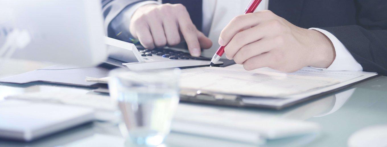 Blog Titelbild ZUGFeRD - ein Geschäftsmann kalkuliert mit Taschenrechner und hält einen Stift in der Hand