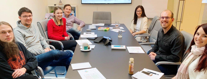 Die Mitarbeiter der World-of-edv sitzen bei ihrem Team Meeting beisammen