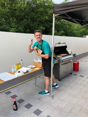 Ein SoftENGINE Mitarbeiter steht mit Grillzange und Würstchen vor einem Grill bei den DevDays 2019