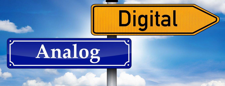 """zwei Schilder """"Analog"""" und """"Digital"""" an einem freistehenden Pfosten vor blauem Himmel und Wolken"""