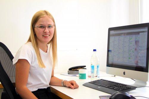 Praktikantin Julia sitzend an ihrem Praktikumsplatz hat Spaß an der Arbeit