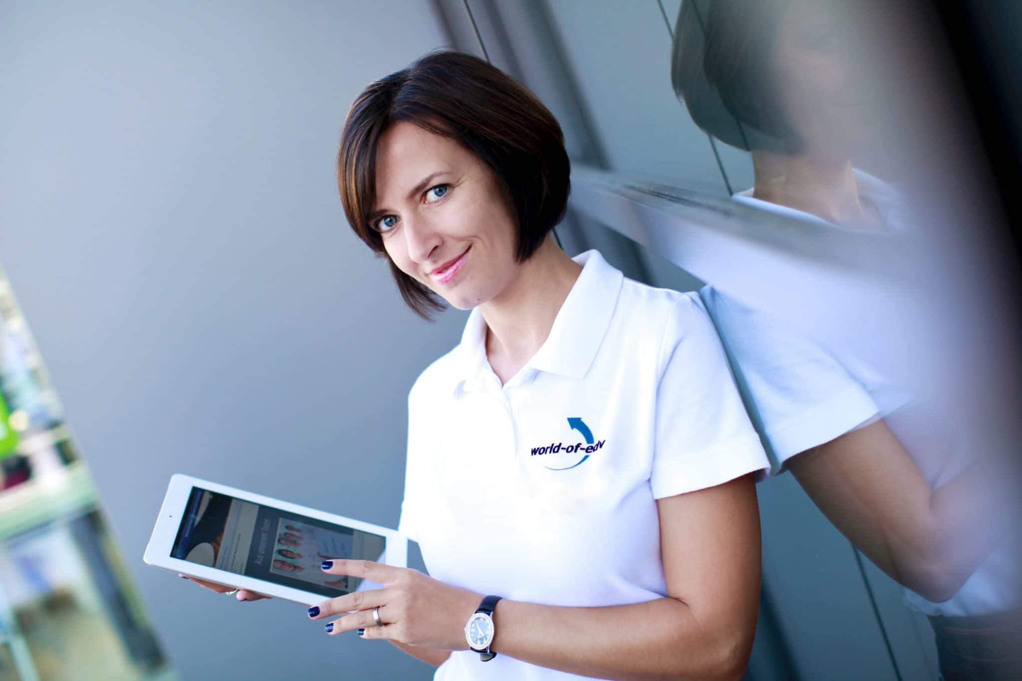 News der World-of-edv präsentiert von Katerina Wagner mit einem Tablet in der Hand